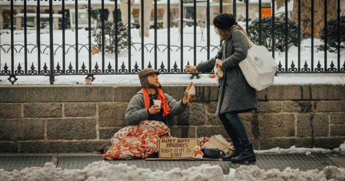Woman donating food to a homeless man